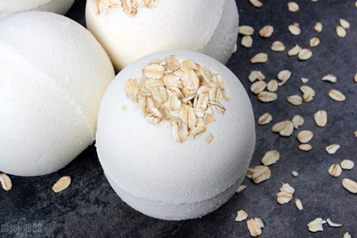 oats bath bombs, white and round, decorated with rolled oats on top, placed on a dark grey surface, with oatmeal flakes strewn about