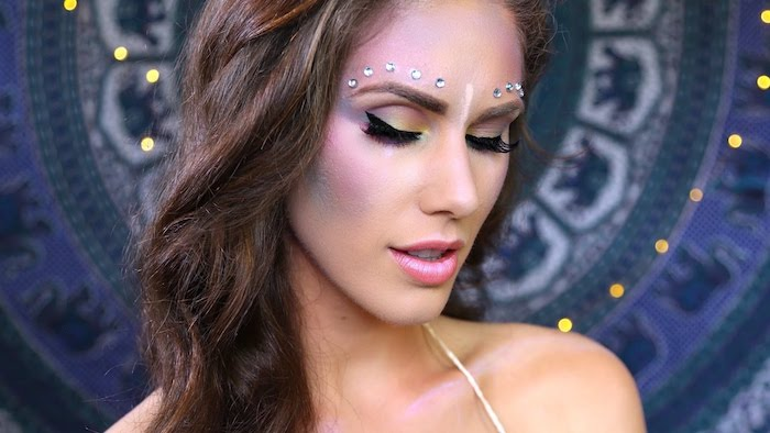 3D pearl-shaped stickers in silver, decorating the forehead of a slim woman, with long wavy brown hair, make up ideas, pink lipstick and black eyeliner, blue and pink blush