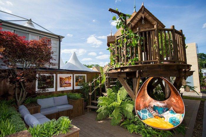 lounging area with two sofas, a multicolored armchair swing, and various plants, small wooden structure, backyard treehouse