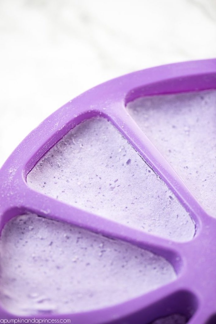 moulding dish in purple, made from plastic, with candy corn-shaped compartments, filled with a violet mixture, bath bomb recipe, on a marble surface