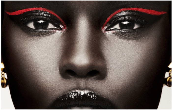 black woman with shiny black lipstick, black mascara and eyeshadow, decorated only with two neon red lines, festival makeup, two gold earrings