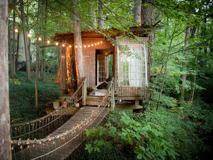 boho hut built around several trees, inside a green forest, construction made from wood, with large windows, treehouse designs, decorated with fairy lights