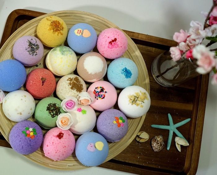 assortment of bath bombs, in different colors, and with various decorations, on a round tray, placed on a rectangular tray, near flowers and shells