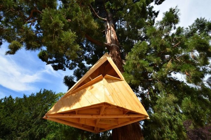 pyramid-shaped construction, made from pale wood, and suspended from a large fir tree, diy treehouse or shelter