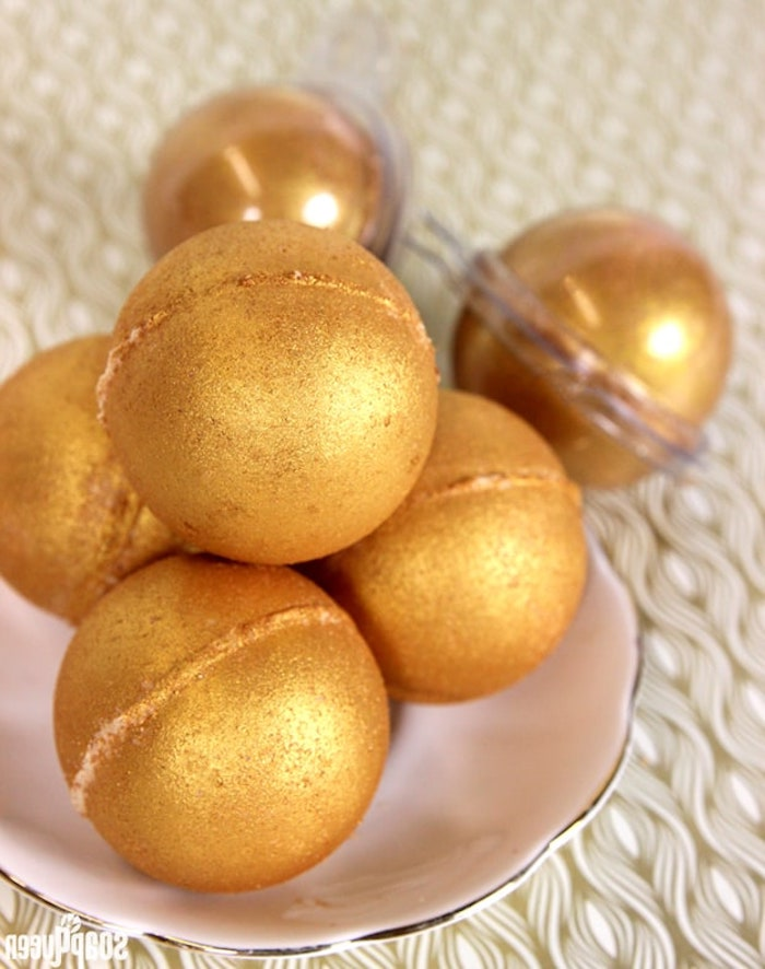 metallic bath bombs, in a sparkly golden color, a few are placed on a small ceramic plate, and two are inside clear plastic wrappers