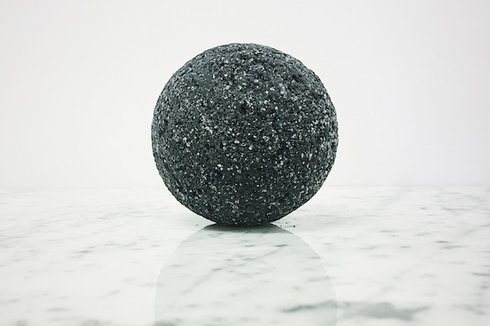 silver glitter on a black bath bomb, with perfectly round shape, placed on glossy, smooth marble surface