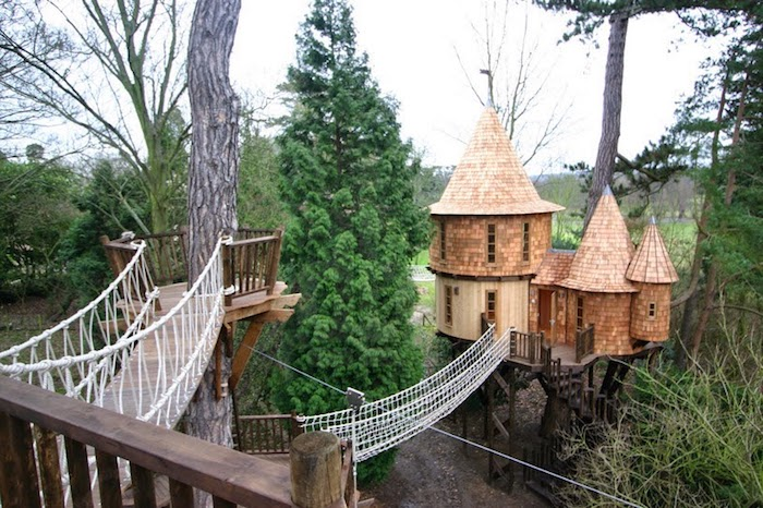 castle-like tree house, with three towers, covered with wooden panels, treehouse ideas, linked to nearby structure, with a bridge made of rope