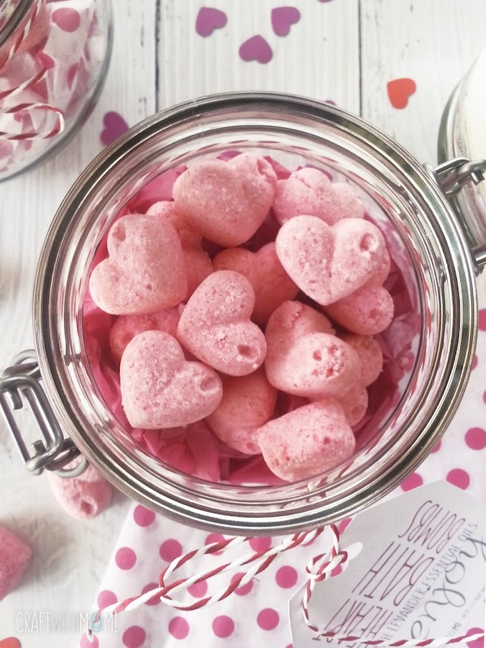jar with a snap lid, filled with diy bath bombs, shaped like small pink hearts, decorated with string and a label, heart-shaped confetti nearby