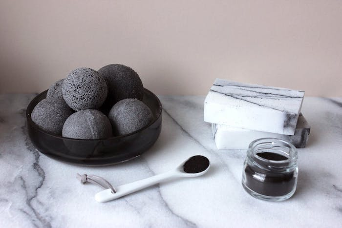 black bath bomb ideas, small jar and spoon, both filled with black powder, on a marble surface, with black dish, containing several dark gray bath bombs