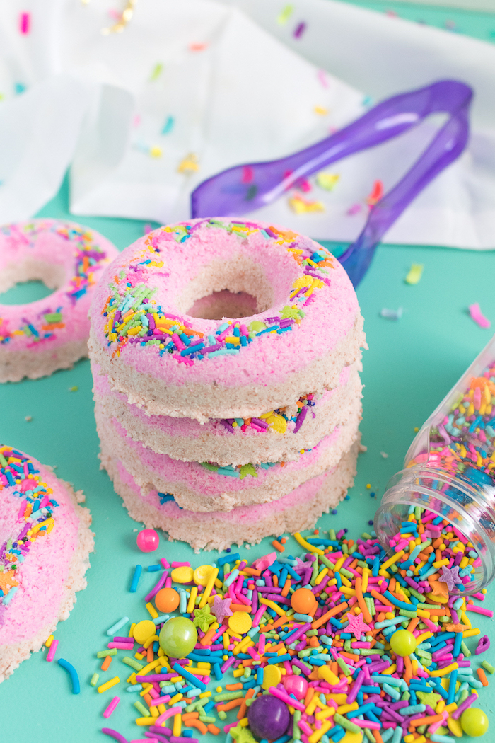 donut-shaped bath bombs, in pale beige and pink, decorated with multicolored sprinkles, four stacked on top of each other
