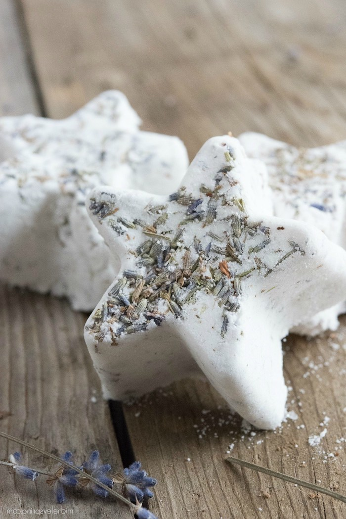 creamy white star-shaped homemade bath bombs, decorated with dried lavender, and placed on a wooden surface