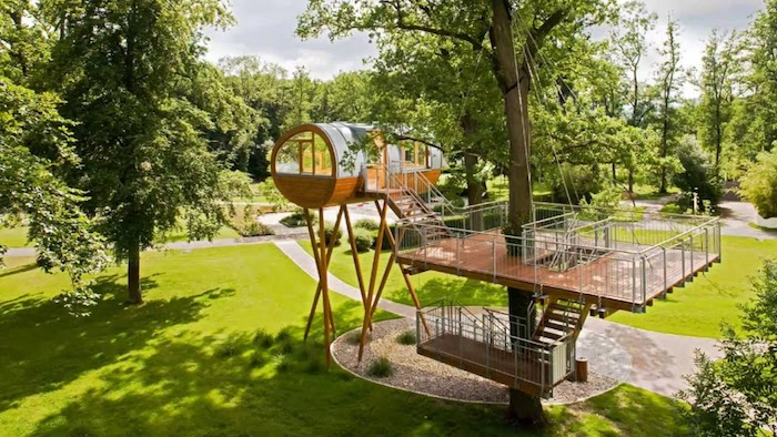 lush green park, with many trees, containing a modern, tubular adult treehouse, made from glass and wood, staircase built around a large tree