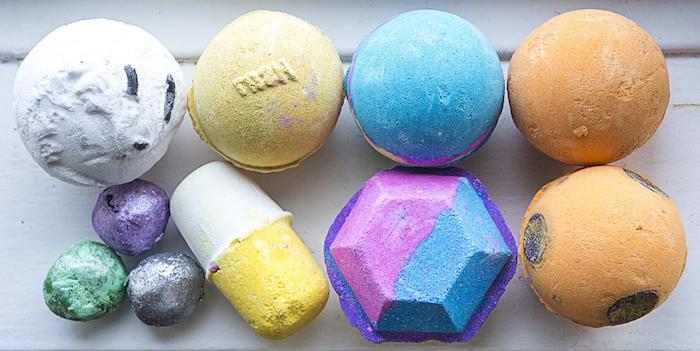 pill and gem-shaped bath bombs, near several round bath balls, in different sizes and colors, white and yellow, blue and orange, green and violet