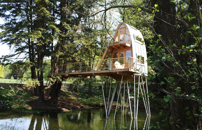 metal beams supporting a modern adult treehouse, with semi oval shape, built in a lake, surrounded by various trees