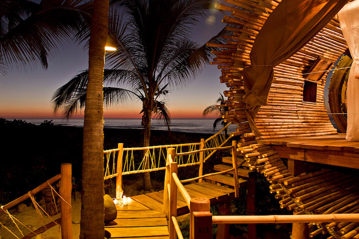 palm trees surrounding a beach tree house, made from bamboo and wood, curtains and lit candles, the sea at dusk in the background, diy treehouse