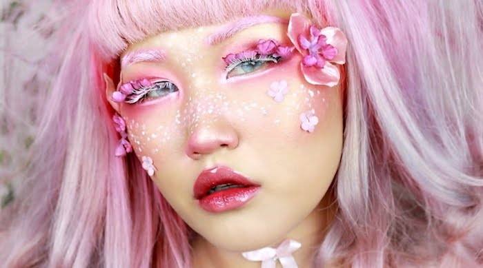 doll-like artistic make up, glossy pinkish-red lipstick, fake eyelashes with white mascara, pink and white face paint, faux flowers stuck on the sides of the face, pastel pink hair with short cropped bangs