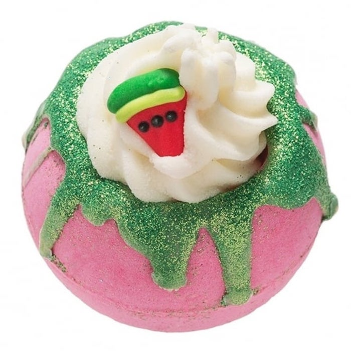 pink and sparkly green bath bomb, decorated with cream-like topping, and a small watermelon slice figurine