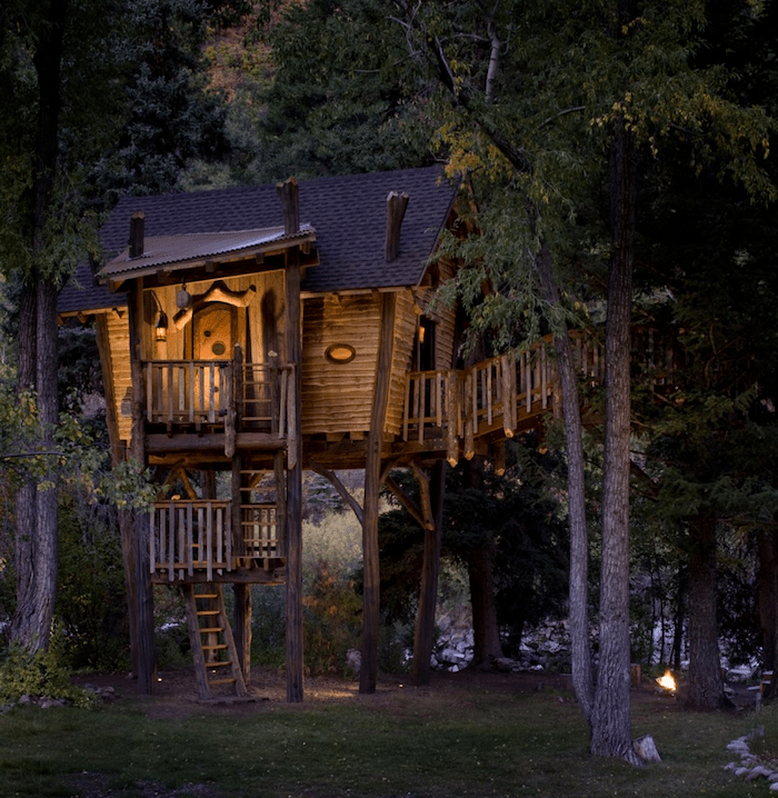 asymmetrical wooden house, built above the ground, and supported by several trees, lit from within, photo taken at night