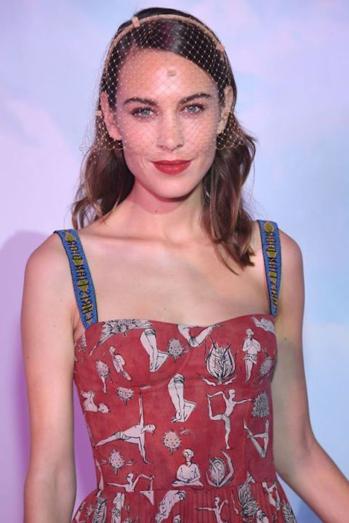 mesh veil worn by alexa chung, in a red dress, with blue straps, and white and black pattern, medium length hairstyles for thin hair, slick side part and wavy ends
