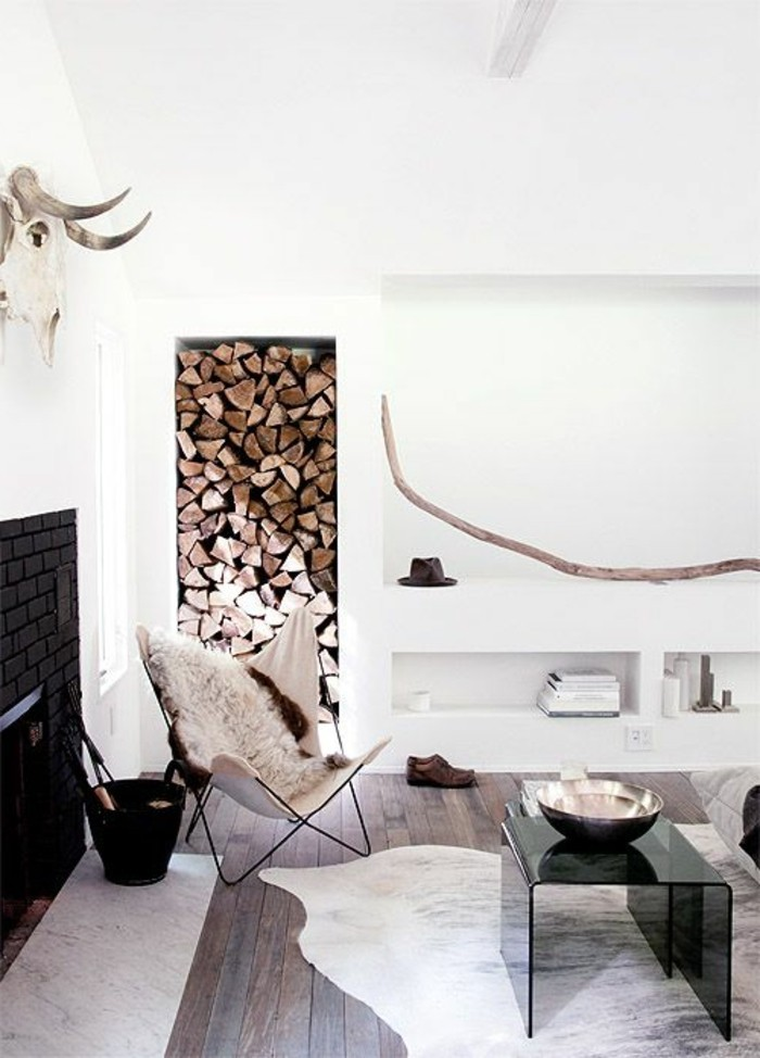 skull of an animal with horns, mounted on a white wall, above a black fireplace, inside a minimalistic, nordic style room, firewood and animal skins