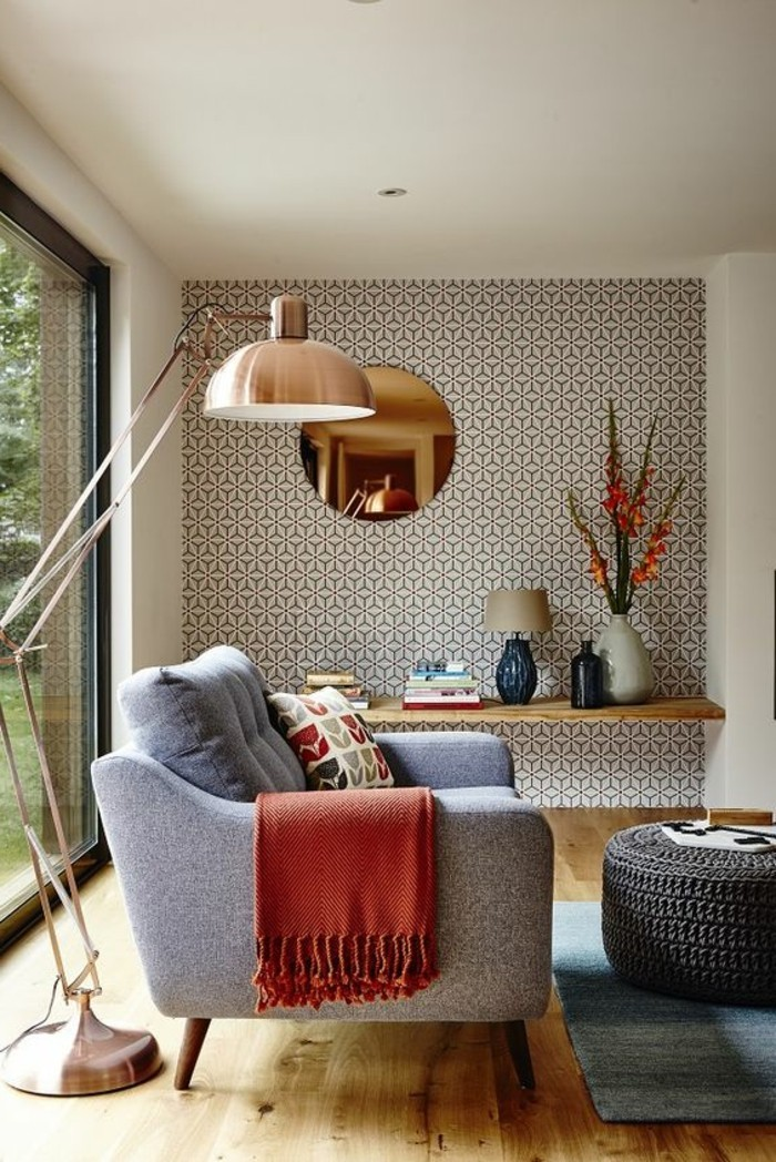 copper-colored lamp, standing over an armchair in grey, with a patterned cushion and a red throw, on a beige wooden floor, near a faded blue rug, and a coffee table