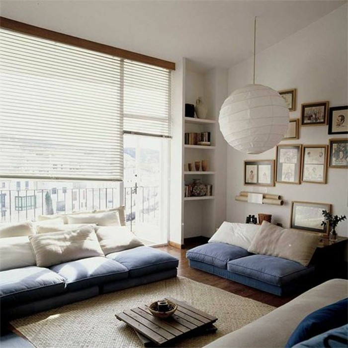 ground level sofa, and matching settee, made from blue and white cushions, placed on the floor, small wooden coffee table, large window with blinds