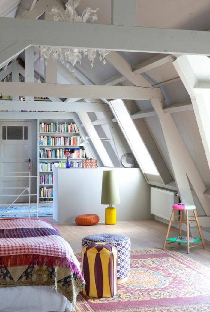 ornamental multicolored rug, inside an attic room, with light laminate floor, white ceiling beams, room design, bed with multicolored cover, and book shelves