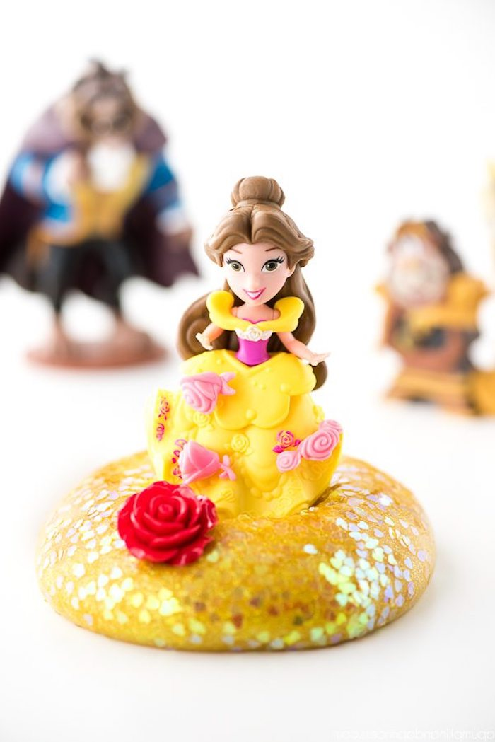 beauty and the beast-themed slime without borax, plastic character figurine, in yellow and pink dress, with brown hair, standing on a pile of yellow goo, covered with iridescent glitter flakes