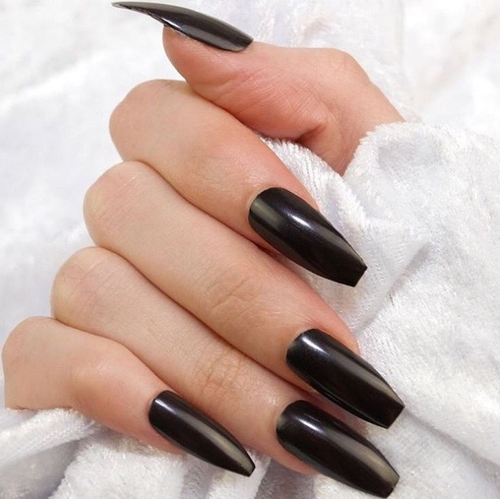 jet black smooth and shiny nail polish, on the long coffin nails, of a hand with folded fingers, holding a white, towel-like fabric