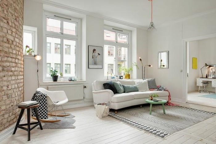 nordic style living room in white, with a brick wall accent, containing a white sofa, with several cushions, a patterned rug in grey, chairs and a turquoise coffee table, room setup ideas