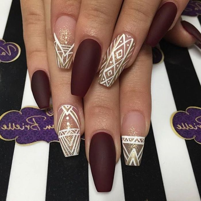 wine red matte nail polish, and clear glossy nail polish, on coffin acrylic nails, decorated with gold glitter, and white motifs, on two hands, one resting on top of the other