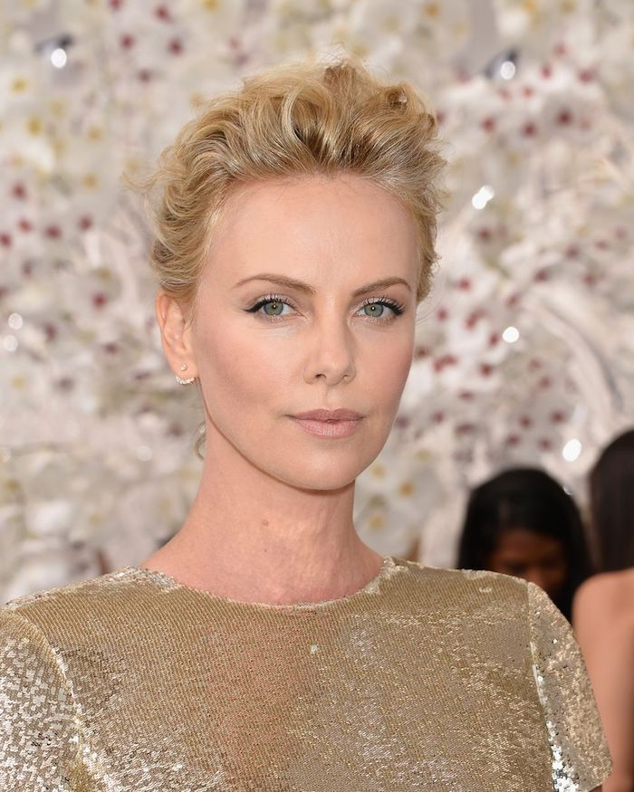 hairstyles for women with thin hair, charlize theron with wavy, short pixie cut, styled upwards like a pompadour, wearing a golden sequin dress