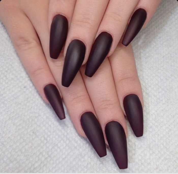 acrylic nail shapes, painted in a dark, cherry red matte nail polish, on two hands, one resting on top of the other, on a white textured surface
