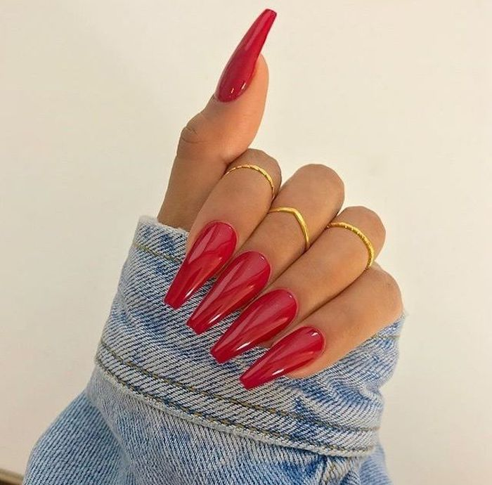 denim sleeve held by a hand, with three thin golden rings, and long and coffin nails, painted in a vibrant red color