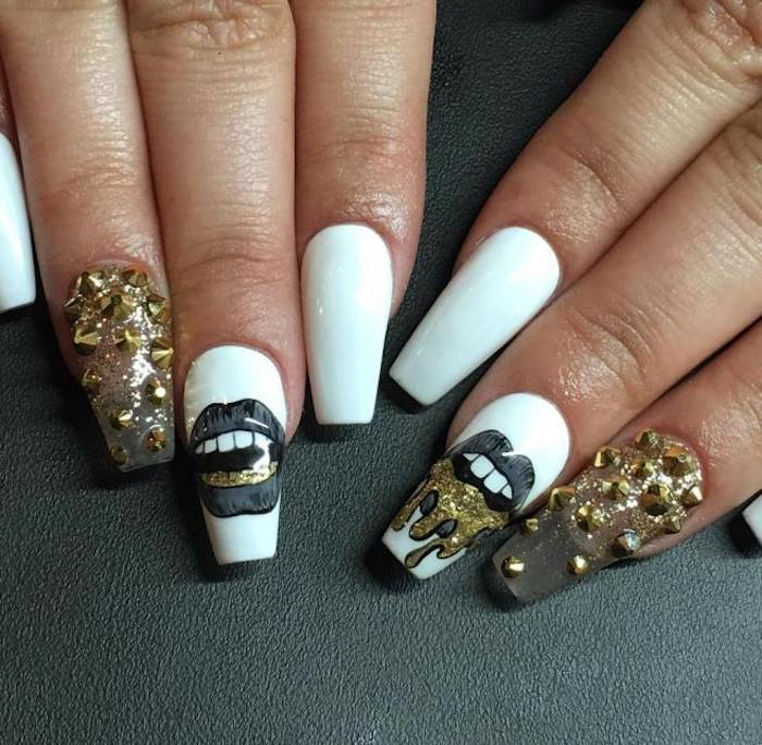 drawings of lips in grey and gold, on the middle finger nails of two hands, the rest of the coffin acrylic nails are pure white, or clear and covered with gold rhinestones