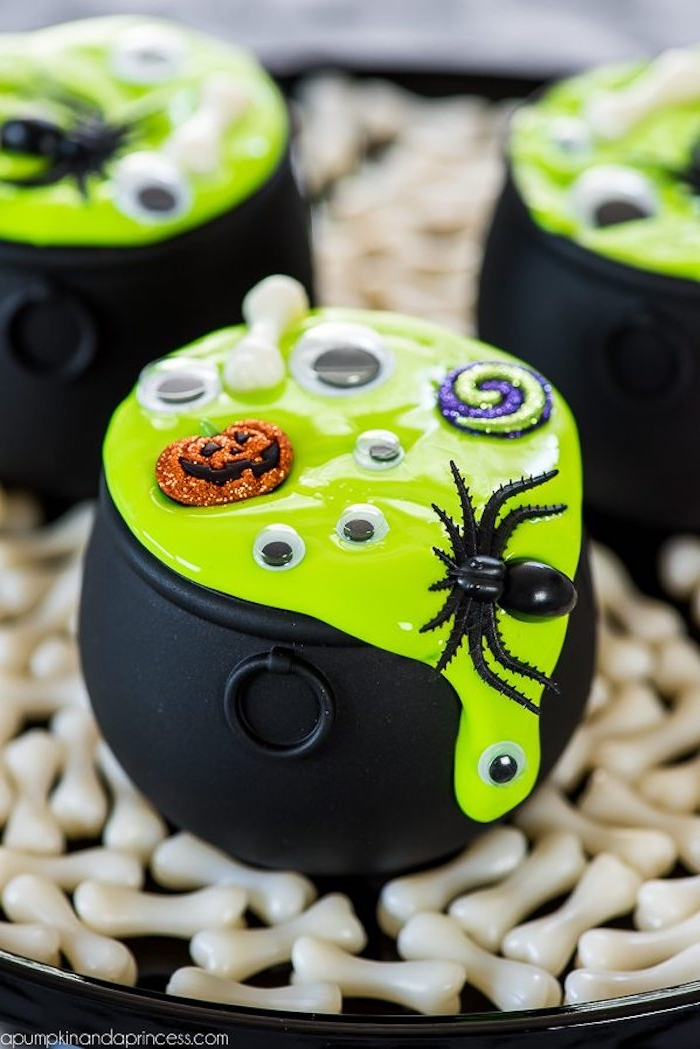 acid green slime, decorated with halloween themed plastic shapes, seeping out of three small black containers, shaped like cauldrons, placed on a black dish, containing small candy, shaped like bones