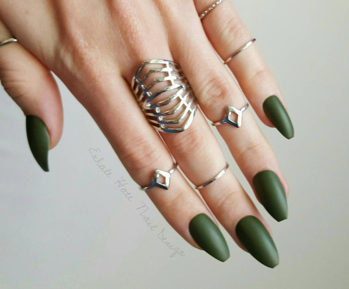 forest green matte nail polish, on a hand with medium long, coffin-shaped manicure, wearing seven different silver rings
