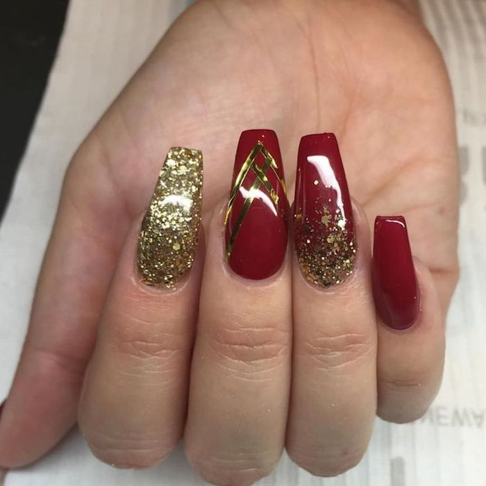 sparkling gold glitter, and four gold stripes, coffin nail designs, on a hand with smooth and shiny, deep red nail polish