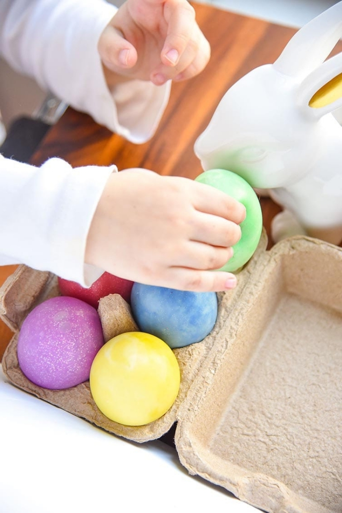 tiny hand holding a green, egg-shaped piece of slime, over an egg carton, containing red and blue, purple and yellow eggs, how to make slime with glue