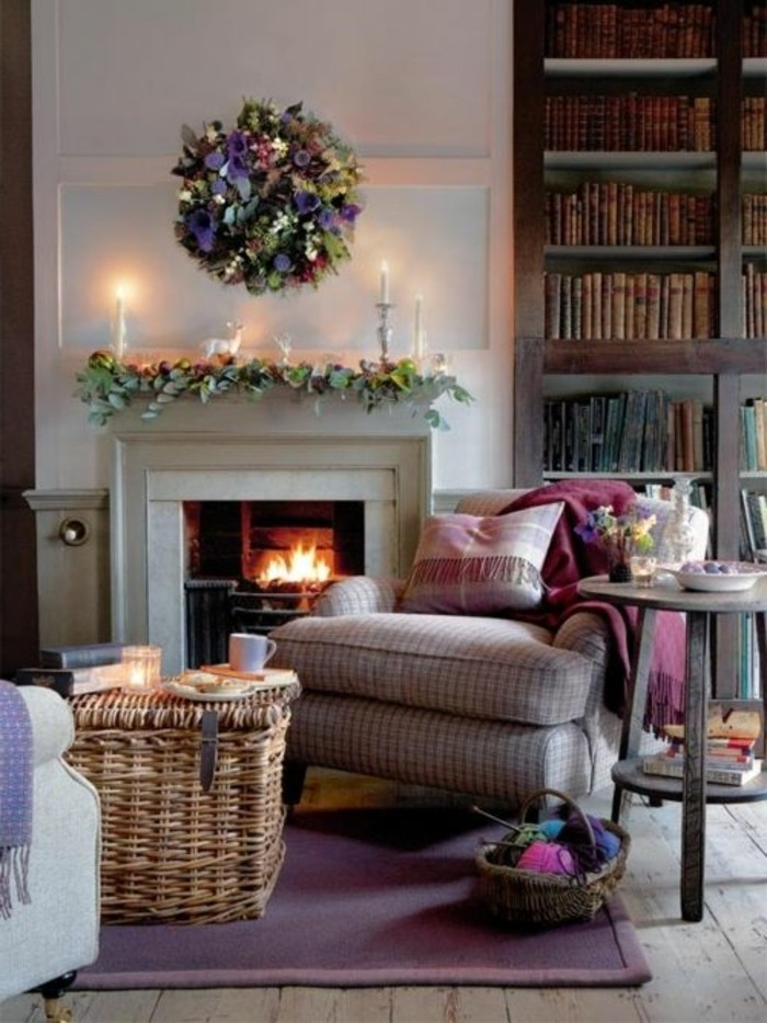 lit fire inside a fireplace, wicker coffee table, and retro armchair, home decor inspiration, dark brown bookshelves, candles and flower decorations