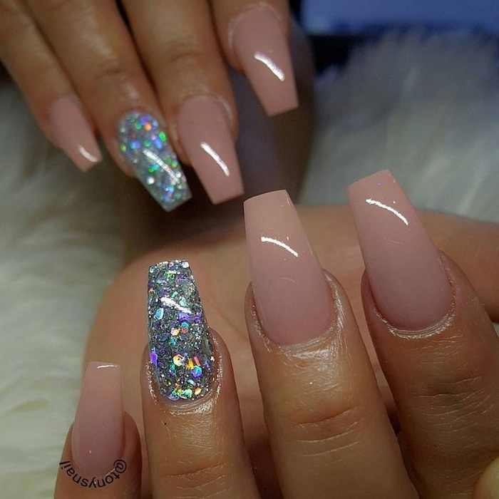 glossy nude pink nails, on two hands with coffin style manicure, both ring finger nails are covered in iridescent glitter flakes
