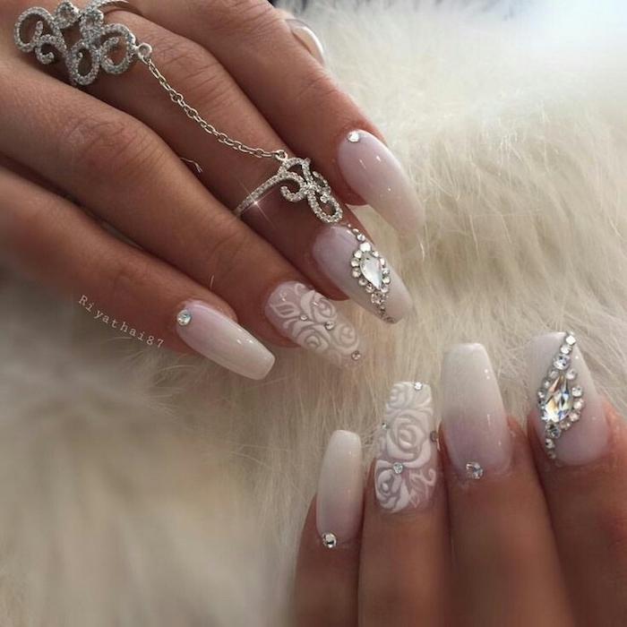 roses painted in white acrylic, on the ring finger nails of two hands, the rest of the nails are white, and decorated with rhinestones