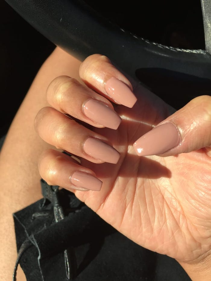 nude coffin nails, in a pinky beige hue, on a hand with folded fingers, seen in close up, near a car's steering wheel