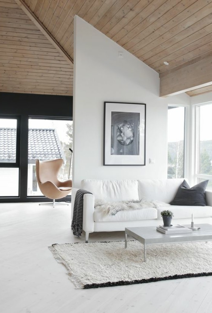 bright space with a wooden vaulted ceiling, large windows and white walls, containing a white sofa, with dark grey cushion and throw, how to decorate a living room