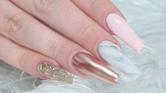 different kinds of nail polish, on four coffin shaped nails, iridescent glitter and rose gold metallic effect, marble-style and plain pastel pink