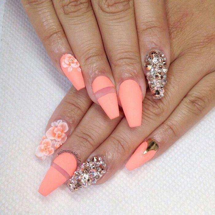peach colored nail polish, decorated with acrylic flowers, and a golden metallic detail, rhinestones and clear stripes, squoval nails