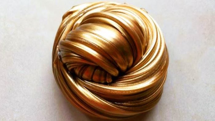 metallic fluffy slime, in a shiny golden color, shaped into a knot-like, twisted round shape, placed on a pale beige surface