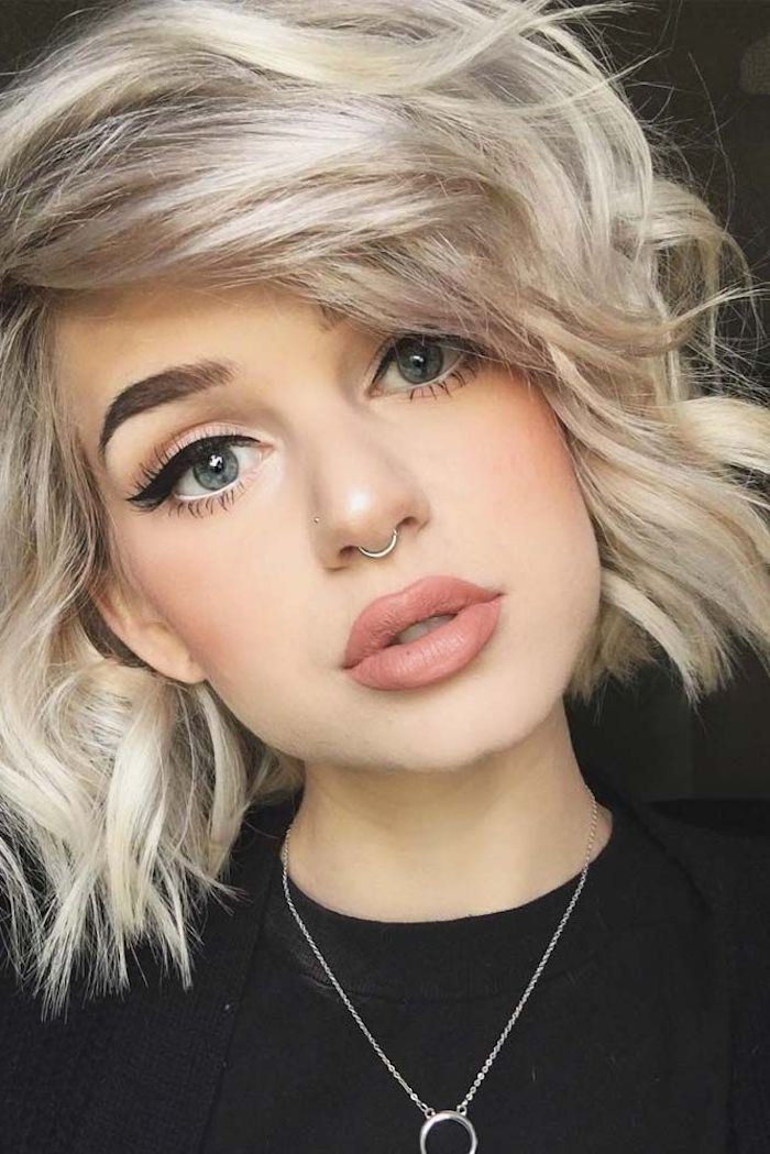 short sassy haircuts, curled platinum bob, with side bangs, on girl with bold black eyeliner, and matte lipstick in nude beige