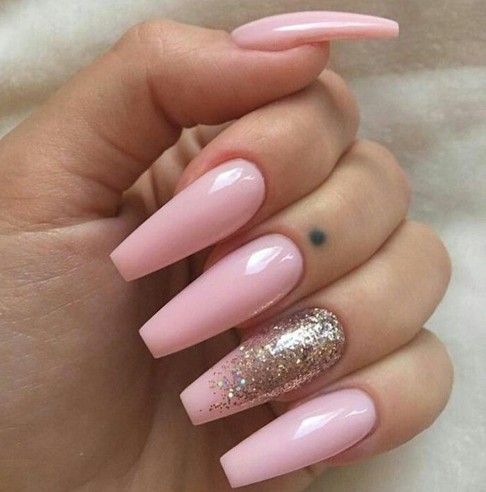 folded fingers with long coffin nails, painted in a pale baby pink hue, the ring finger nail is decorated with iridescent glitter