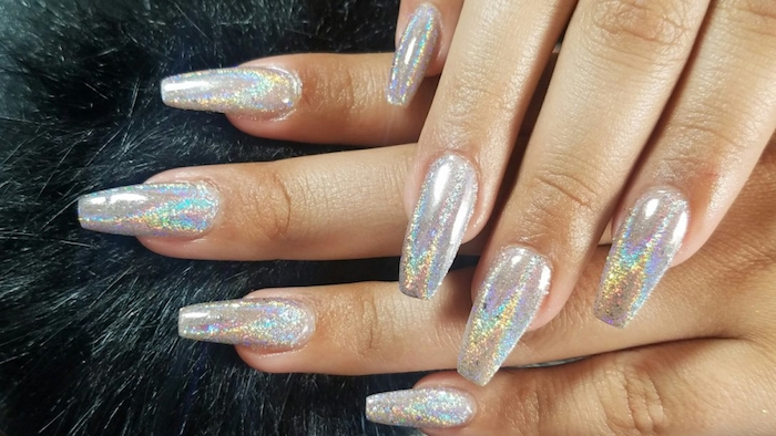 iridescent hologram nails, with soft yellow, orange and pale blue reflections, on two hands, resting on a black, fur-like surface, acrylic nail shapes